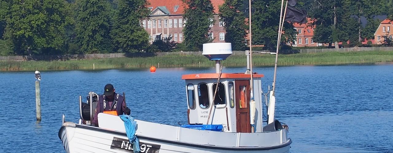 Fiskekutter på vej ind - morgenstemning ved Præstø Havn med Nysø Gods i baggrunden