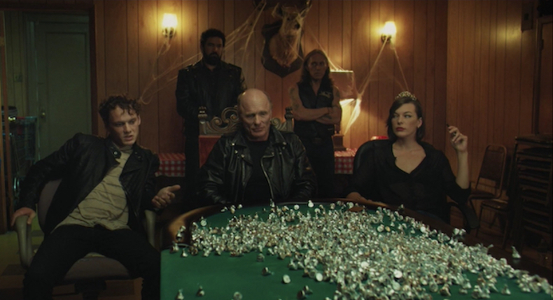 Cymbeline's court rejecting the tribute. Ed Harris as Cymbeline, Milla Jovovich as the Queen, and Anton Yelchin as Cloten